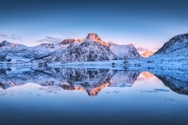 雪に覆われた山々とカラフルな空が夕暮れ時の水に反映