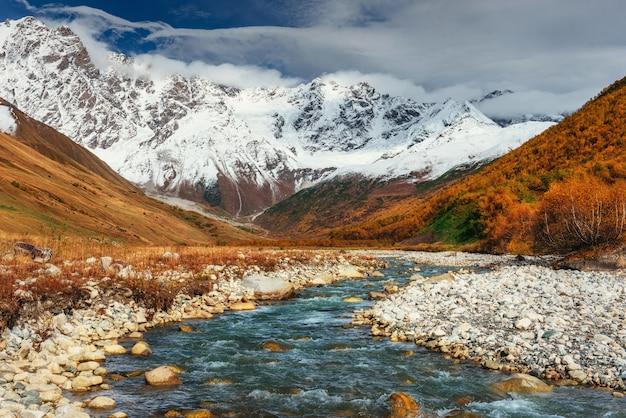 Снежные горы и шумная горная река. грузия, сванетия. евро