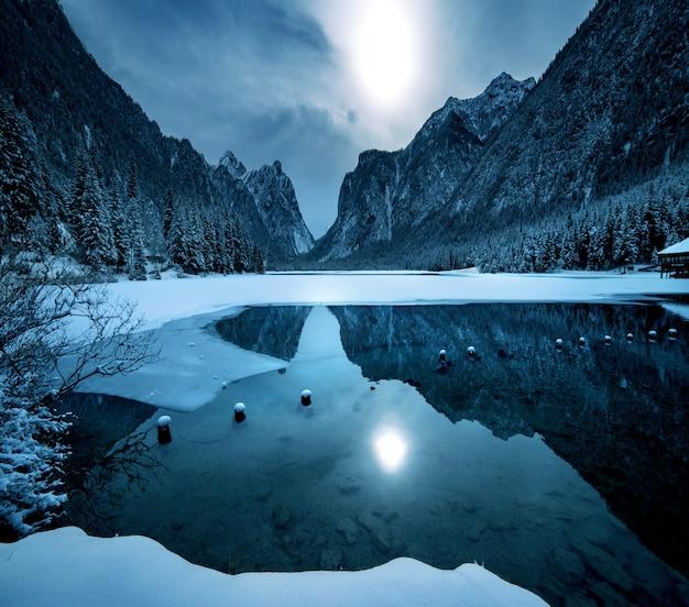 Dolomiten의 눈 덮인 산이 아래 호수에 반영