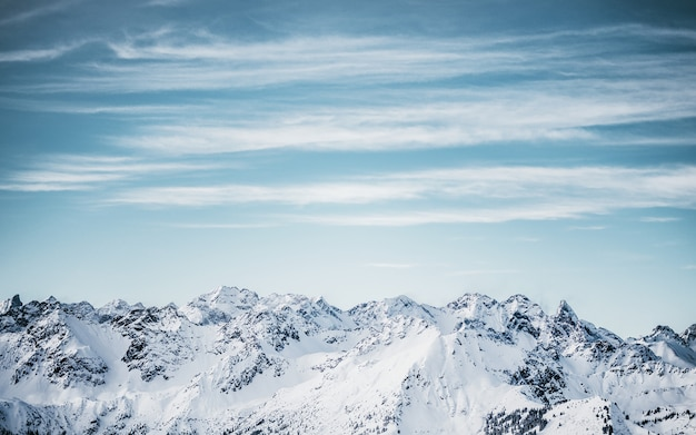 Snowy mountains under a blue cloudy sky at daytime