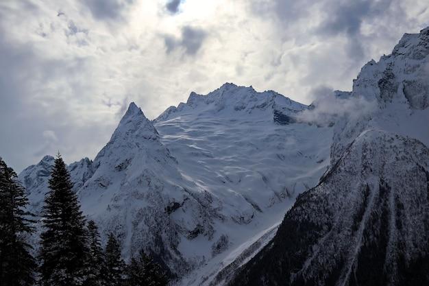 雪に覆われた山々は雲の青い空にピークコーカサス