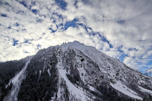 雪山は雲の青い空にピークコーカサス