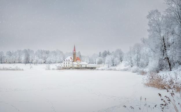 古い宮殿の雪に覆われたパノラマビュー。美しい自然の風景の中に古いマルタの宮殿と白い雪の風景。ガッチナ。ロシア。