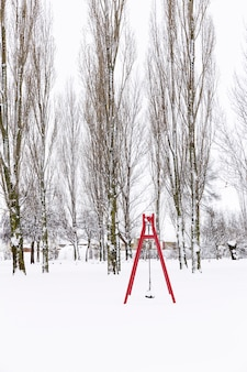 Snowy park with swings and trees