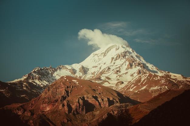 夜明けのジョージアのカズベク山の雪に覆われた山頂