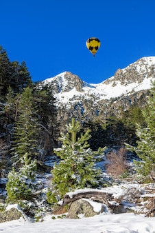 Snowy pyrenees mountains with yellow hot air balloon