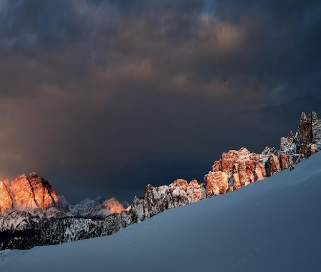 暗い曇り空の下でイタリアアルプスのドロミテンで雪に覆われた岩