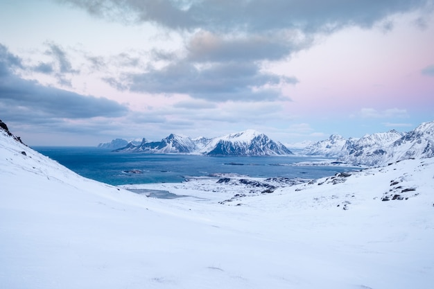 Snowy slope in valley with arctic ocean on coastline on winter