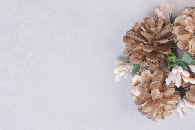 Ramo di abete innevato con pigne isolate sul tavolo bianco.