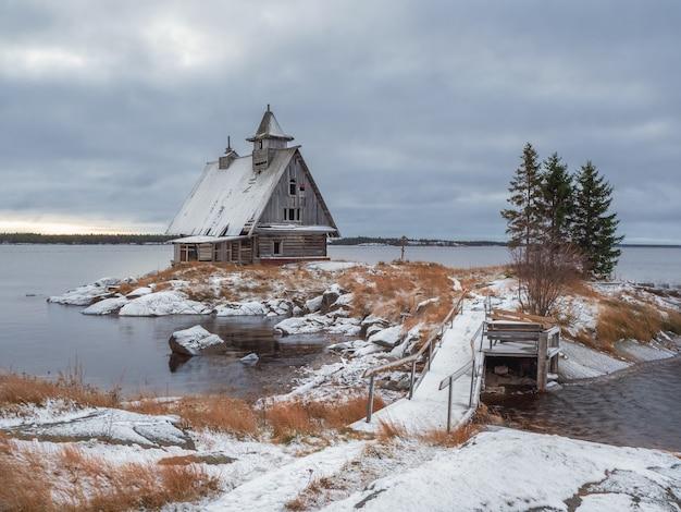 러시아 마을 rabocheostrovsk의 해안에 정통 영화관이있는 눈 덮인 겨울 풍경. 영화 촬영을 위해 지어진 목조 예배당.