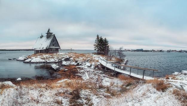 러시아 마을 rabocheostrovsk의 해안에 정통 집 눈 덮인 겨울 풍경. 파노라마 뷰.