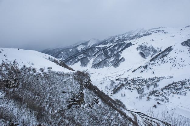 太陽の日に雪に覆われた冬の山々。ジョージア州コーカサス山脈、スキーリゾートグダウリから