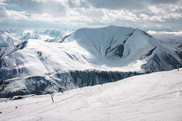 Snowy winter mountains in sun day. caucasus mountains, georgia, from ski resort gudauri