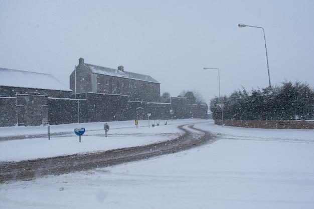 눈보라 동안 눈 덮인 겨울 도로. 폭설 폭풍.