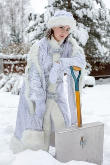 Snowy winter. a young woman dressed as a snow maiden with a shovel rakes snow.