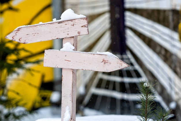 Snowy wooden signpost with two nlank arrows on a colorful blurry surface