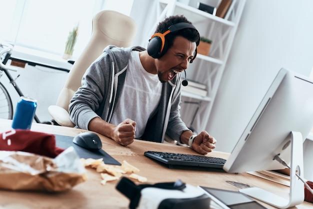 とても怒っています!コンピューターを使用し、家で時間を過ごしながら叫んでカジュアルな服を着た猛烈な青年