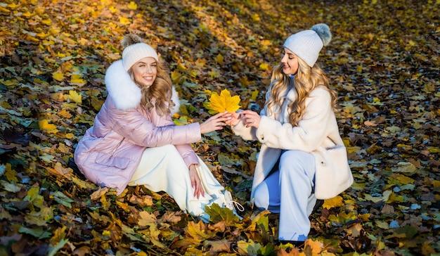 너무 아름다워. 아늑하고 편안합니다. 가을 시즌 패션. 여성의 아름다움과 스타일. 가 숲에 긴 머리를 가진 아름 다운 여자. 마른 낙된 엽 배경에 소녀입니다. 따뜻한 옷을 입으십시오.
