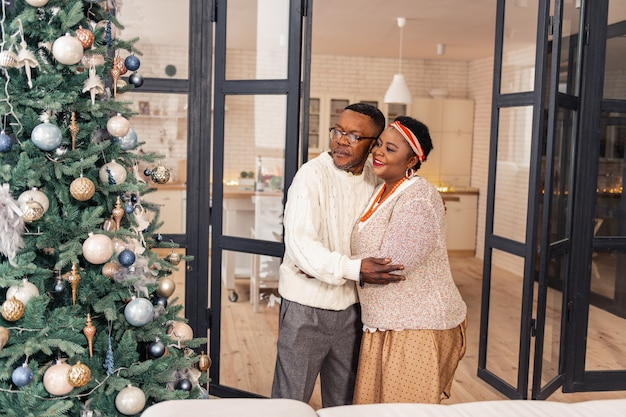 So beautiful. joyful african couple standing in front of the christmas tree while looking at it
