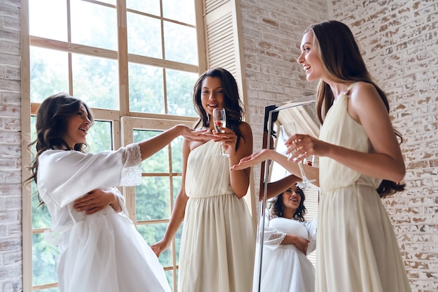 Такая красивая! две привлекательные молодые женщины улыбаются, глядя на обручальное кольцо невесты, стоя у окна вместе
