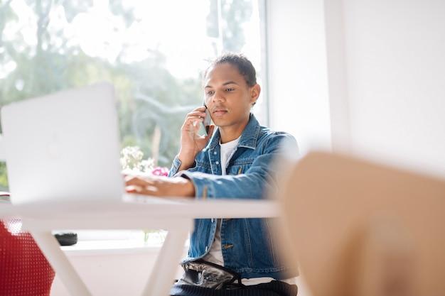 とても忙しい。コンピューターで働いていて、電話で彼の対話者の話を聞いている気配りのある男性