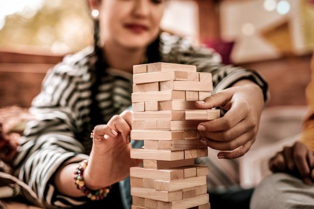 とても注意してください。ジェンガをプレイしながら笑顔を保つ気配りのあるブルネットの女の子