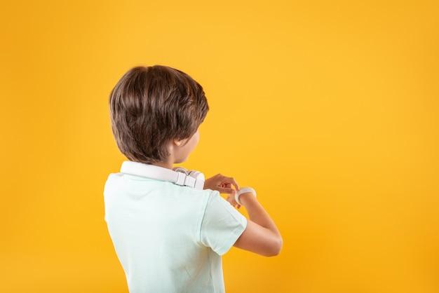 とても賢い。彼の時計を考えて見ている愛らしい黒髪の少年