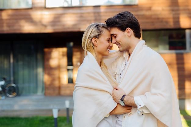 Так холодно. счастливая пара в восторге, стоя вместе в одном пледе