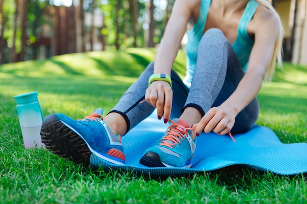 とても快適です。美しいフィットの若い女性が着用している新しい青いスポーツシューズのクローズアップ