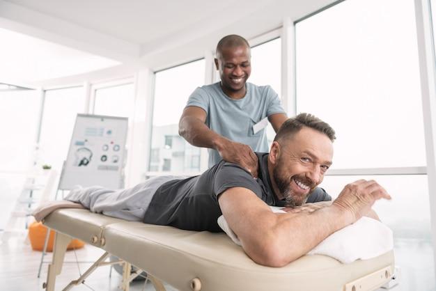 Так удобно. положительно обрадованный симпатичный мужчина, лежащий на медицинской кушетке в отличном настроении