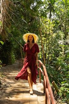 とてもかわいい。木製の小道を歩きながら笑顔を保つ魅力的な若い女性