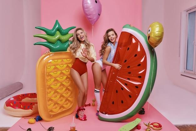 Как мило. две привлекательные молодые женщины в купальных костюмах играют с фруктовыми украшениями в полный рост