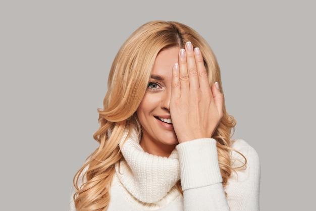 とてもかわいい!カメラを見て、灰色の背景に立っている間、手で顔の半分を覆う遊び心のある若い笑顔の女性