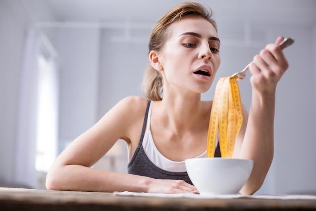 Так вкусно. безрадостная молодая женщина сидит за столом, делая вид, что ест сантиметровую ленту
