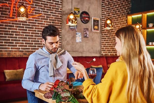 とてもおいしい夕食。青いシャツを着た男がガールフレンドと食べて話している。赤いバラがテーブルの上に横たわっています。マスタードセーターの金髪の若い女性