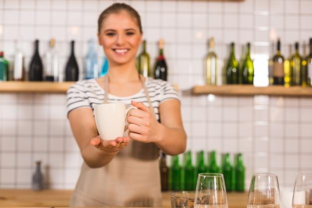 Так вкусно. селективный фокус чашки с чаем, которую держит приятная милая довольная женщина, стоя у стойки