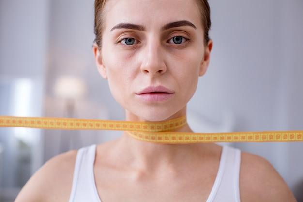 Так подавлен. портрет грустной молодой женщины, смотрящей на вас, держа сантиметровую ленту