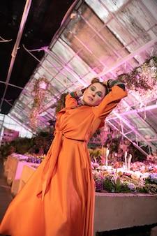 とても夢のような。温室に立ちながら夢のような表情をしている美しい素敵な女性