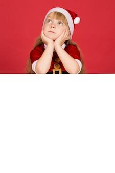 Такой мечтательный сегодня. вертикальный портрет маленькой девочки, мечтающей смотреть вверх, лежа на большом пустом плакате с copyspace