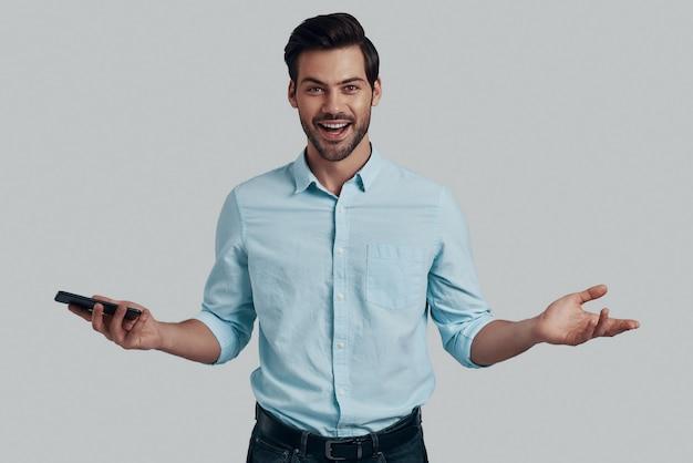 とても簡単!腕を伸ばしたまま、灰色の背景に立っている間カメラを見ているハンサムな若い男