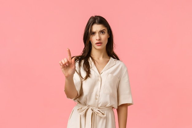 Not so fast, i disagree. displeased and disappointed serious-looking pissed caucasian girlfriend shaking finger in disapproval and negative reply, give warning, standing pink wall