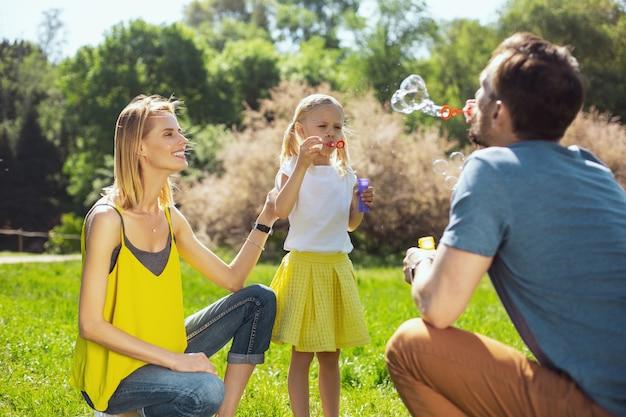 엄청 웃겨. 작은 딸과 함께 웃고 비누 거품을 불고 돌보는 부모에게 경고