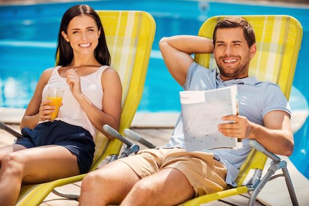 Так хорошо ничего не делать! счастливая молодая пара отдыхает вместе, сидя на шезлонгах у бассейна