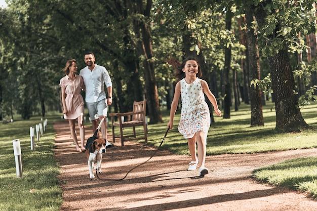 함께여서 너무 좋아요! 공원에서 부모와 함께 걷는 동안 개가 뛰고 웃고 있는 귀여운 소녀의 전체 길이