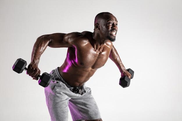 だから翼を育てる。灰色の背景の上の若いアフリカ系アメリカ人のボディービルダーのトレーニング。ウェイト付きのスポーツウェアの筋肉のシングル男性モデル。スポーツ、ボディービル、健康的なライフスタイルの概念。