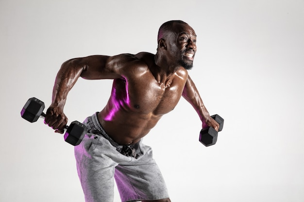 So growing the wings. young african-american bodybuilder training over grey background. muscular single male model in sportwear with weights. concept of sport, bodybuilding, healthy lifestyle.