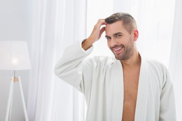 とてもハンサムな。あなたを見ながら彼の髪に触れる素敵なハンサムな男