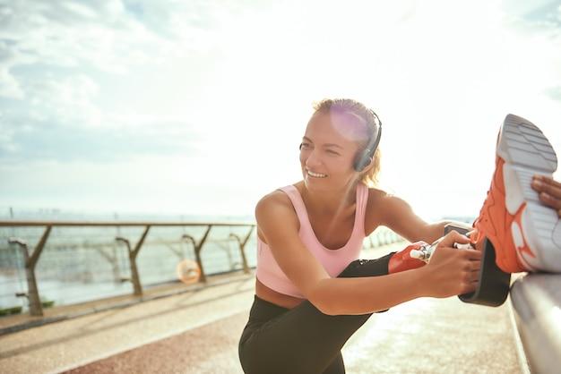 Так счастлив крупным планом веселой женщины-инвалида в наушниках, протягивающей протез ноги и слушающей