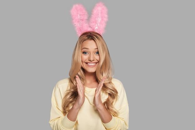 Так счастлив! возбужденная молодая улыбающаяся женщина в розовых кроличьих ушах хлопает в ладоши и смотрит в камеру, стоя на сером фоне