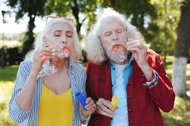 So happy. positive elderly couple blowing soap bubbles while enjoying themselves